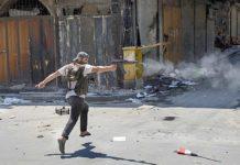 Un rebelde sirio dispara su rifle por las calles del distrito de Bab Al-Nasr. / AFP