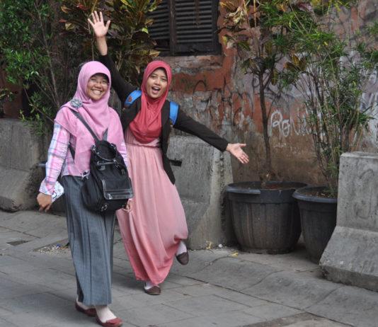 Dos mujeres saludan y caminan por las calles de Yakarta. / Víctor de Currea-Lugo