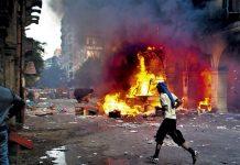 Un seguidor del presidente derrocado, Mohamed Mursi, pasa frente a un vehículo quemado en la plaza Ramses en El Cairo, uno de los epicentros de las protestas y la represión del ejército. / AFP